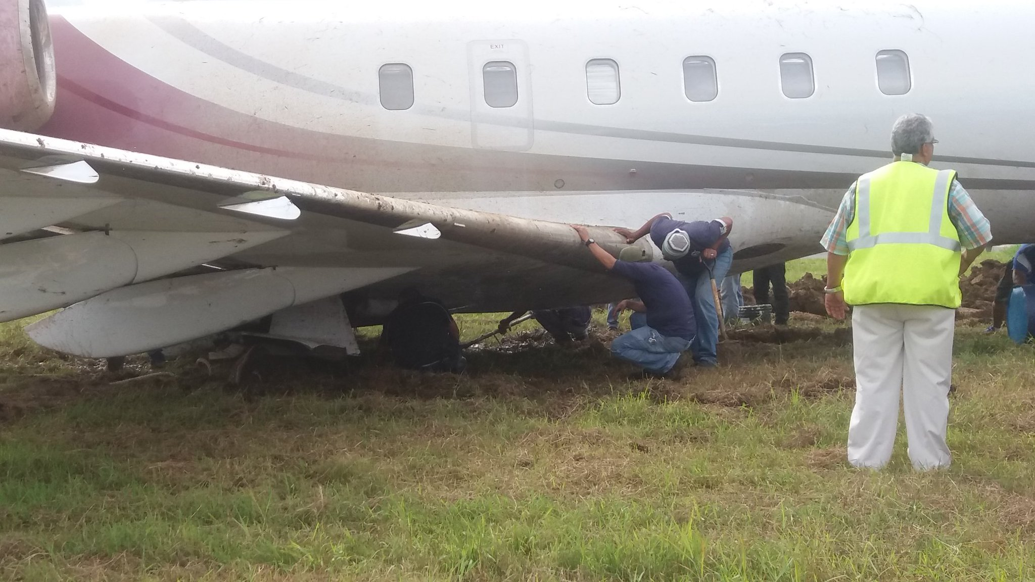 Image shows airport workers attempting extricate a Bombardier jet that skidded off the runway while landing at Albrook airport in Panama City.