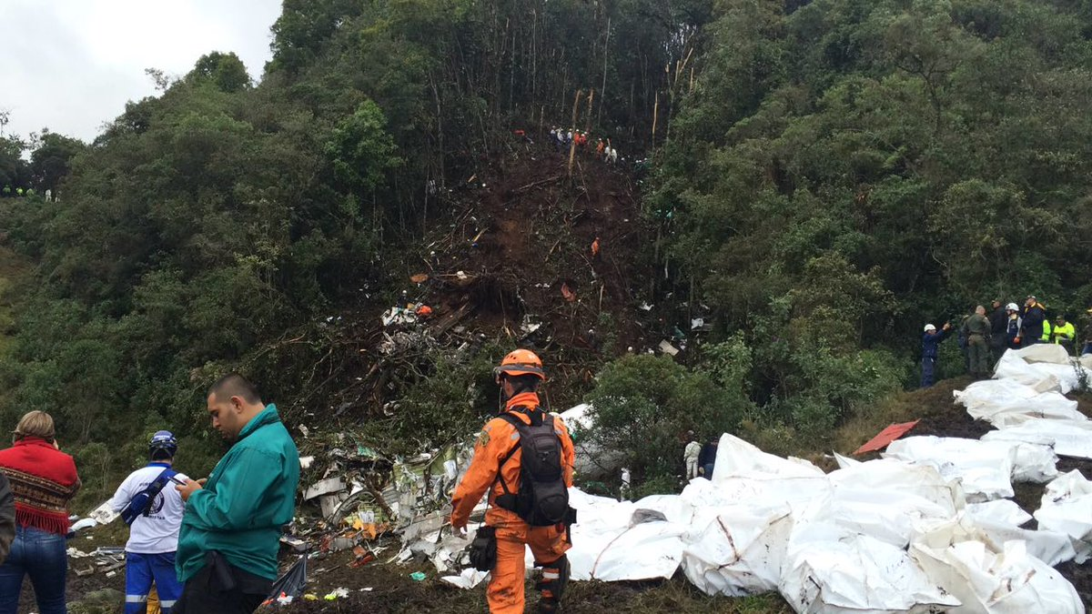 Colombian rescue workers recover bodies from the hillside south of Medellin where a plane carrying a Brazilian soccer team crashed.
